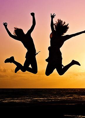 Två unga människor som hoppar upp i solnedgång på stranden.